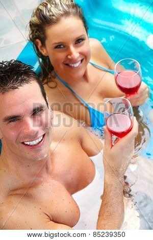 Young couple relaxing in hot tub. Summer vacation.
