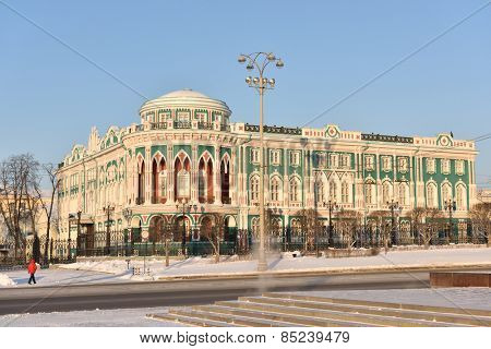 YEKATERINBURG, RUSSIA - JANUARY 2, 2015: Man near the House of N. I. Sevastianov in a winter day. Built in the first quarter of XIX century, now it is one of the most notable landmark of the city