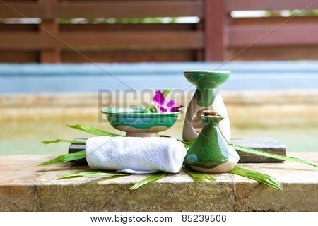 Arrangement of spa treatment products made out of massage oil in ceramic bottle, aromatherapy, scented oil and towel by poolside.