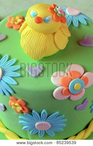 Close  up of an Easter fondant cake with an Easter chick on top.