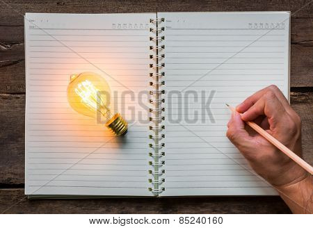 Hand write over Note book and light bulb