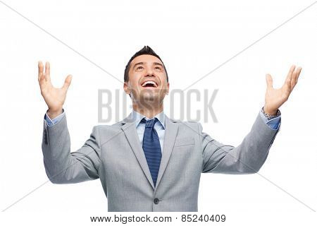 business, people and office concept - happy businessman in suit with raised hands laughing and looking up
