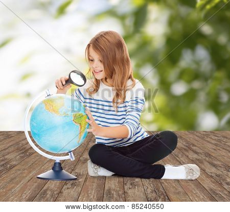 education, travel, childhood, geography and school concept - happy little student girl looking at globe with magnifier over green background