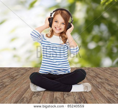 music, childhood, people and technology concept - happy girl with headphones listening to music over greed background