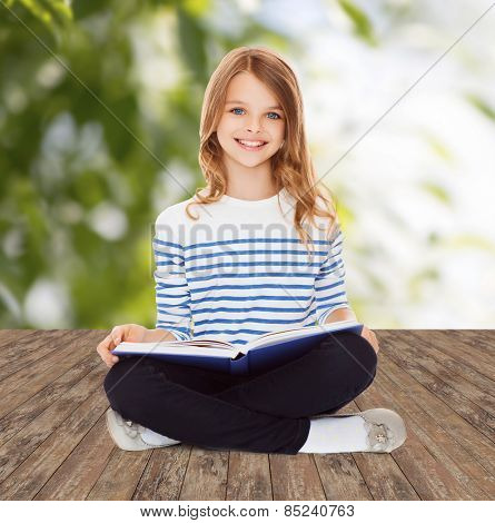 education, childhood, people and school concept - little student girl studying and reading book over greed background