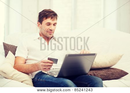 online or internet shopping concept - smiling man with laptop and credit card at home