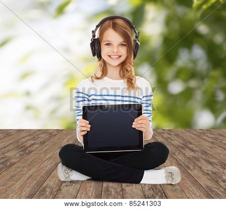 music, technology, people and childhood concept - happy girl with headphones showing tablet pc computer blank screen over greed background
