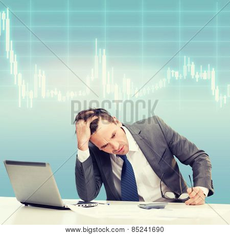 business, office and money concept - stressed businessman in black eyelgasses with laptop computer, papers, calculator and forex chart