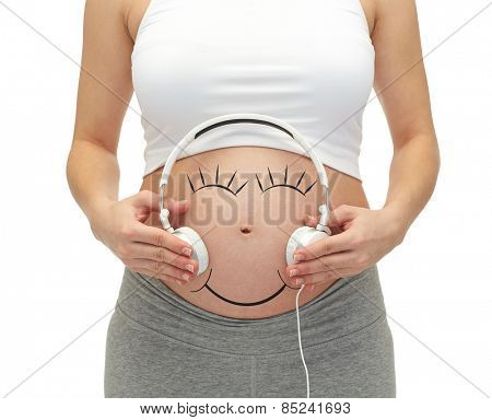 pregnancy, people, music, technology and expectation concept - close up of happy pregnant woman applying headphones to bare tummy