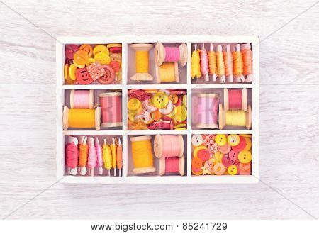 Collection Of Yellow, Red, Pink Spools  Threads  Arranged In A White Wooden Box
