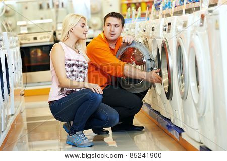 Young man choosing washing machine in home appliance shopping mall supermarket
