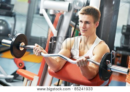athlete man workout biceps brachii muscles exercises with training weight in fitness gym