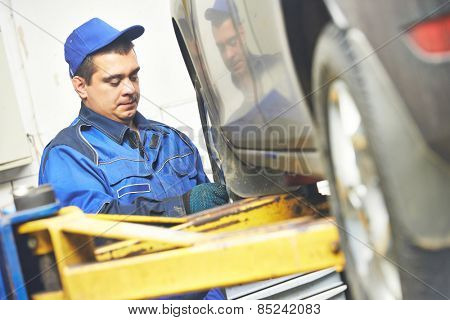 auto repairman mechanic working in car auto repair or maintenance shop service station