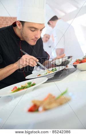 Chef in restaurant kitchen preparing dish