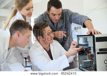 Students in computing class with teacher fixing hardware