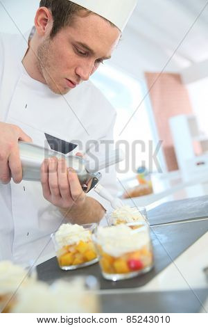Pastry cook spreading whipped cream on dessert