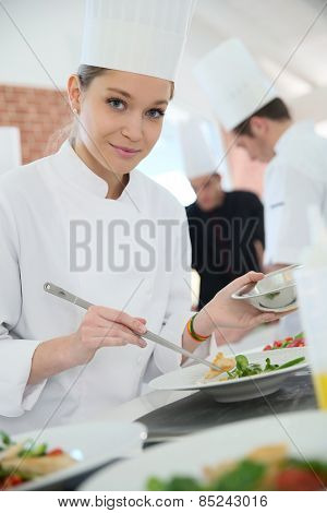 Girl in cooking training class preparing dish