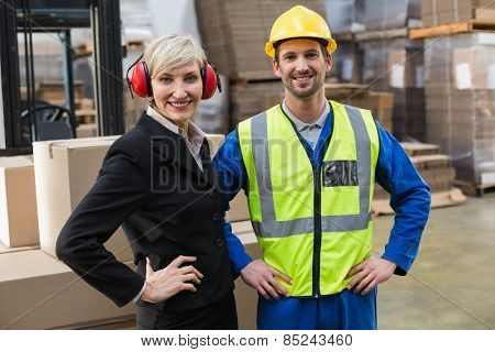 Warehouse worker and his manager with hands on hips in a large warehouse