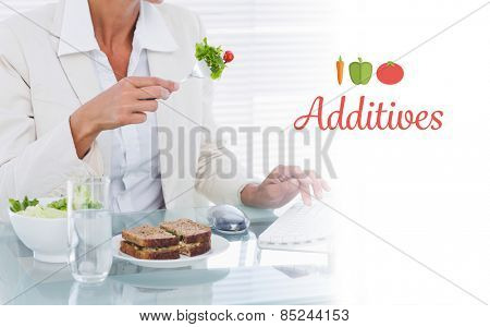 The word additives against businesswoman using computer while eating salad at desk