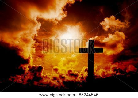 Wooden cross against orange sky
