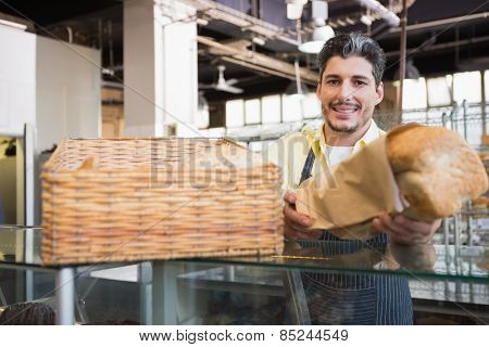 Smiling server in apron offering a bread at the bakery