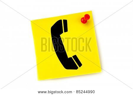Telephone against yellow pinned adhesive note
