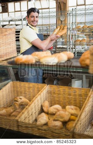 Cheerful waiter in apron holding baguettes at the bakery