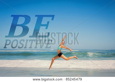Fit woman jumping gracefully on the beach against be postive