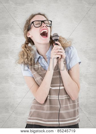 Geeky hipster woman singing into a microphone against white background