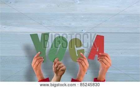 Hands holding up yoga against bleached wooden planks background