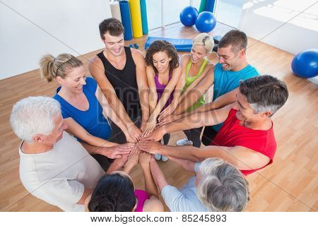 High angle view of fit people stacking hands at health club
