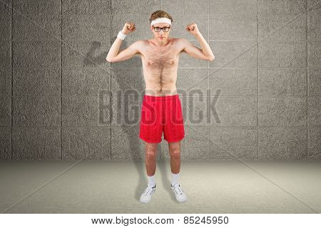 Geeky shirtless hipster flexing biceps against grey room