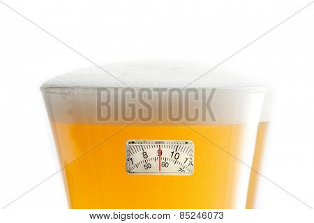 weighing scales against glass of beer