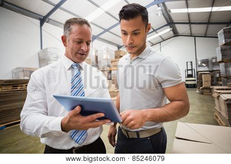 Warehouse manager using tablet pc with colleague in a large warehouse