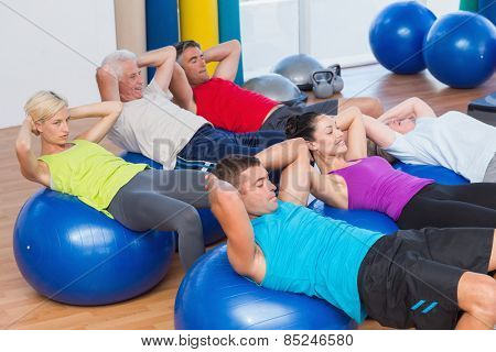 Determined people stretching on exercise balls in fitness club