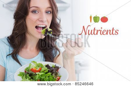 The word nutrients against brunette eating healthy salad