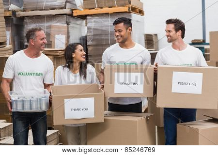 Happy team of volunteers holding donations boxes in a large warehouse