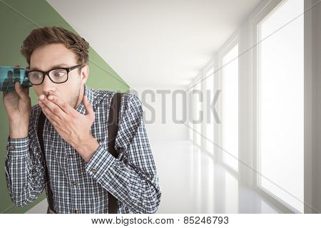 Geeky businessman eavesdropping with cup against modern white and green room with window