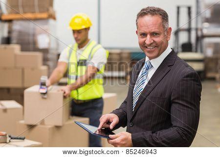 Portrait of male boss using digital tablet in warehouse