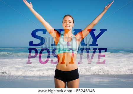 Fit woman standing on the beach with arms up against stay positive