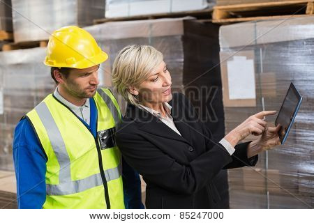 Warehouse worker and manager using tablet pc in a large warehouse