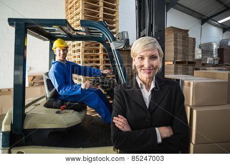 Smiling warehouse manager standing with arms crossed in a large warehouse