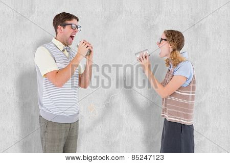 Geeky hipster couple speaking with tin can phone against white background
