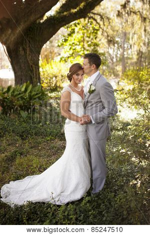 newly married couple having intimate moment in garden, full length portrait