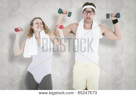 Geeky hipster couple lifting dumbbells in sportswear against white background