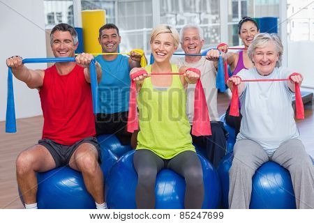 Portrait of happy people on fitness balls exercising with resistance bands in gym class