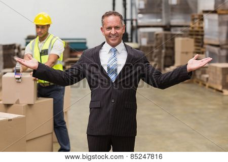 Smiling boss with hands out in a large warehouse