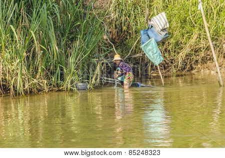 CHAU DOC, VIETNAM - JANUARY 2, 2013: Rural life in Mekong delta- Local woman washes clothes in Bassac River