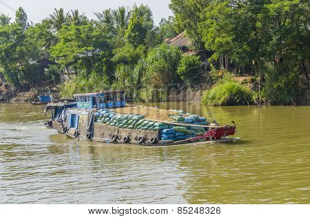 CHAU DOC, VIETNAM - JANUARY 2, 2013: Rural life in Mekong delta- Barge transports rice on Bassac River
