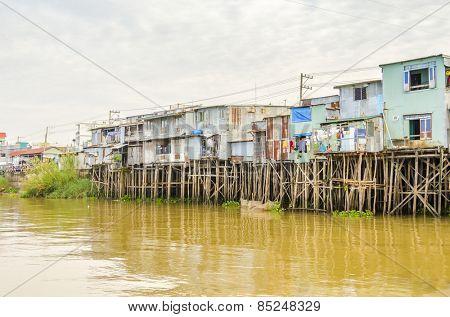 CHAU DOC, VIETNAM - JANUARY 2, 2013: Houses on stilts at the riverside of Bassac River